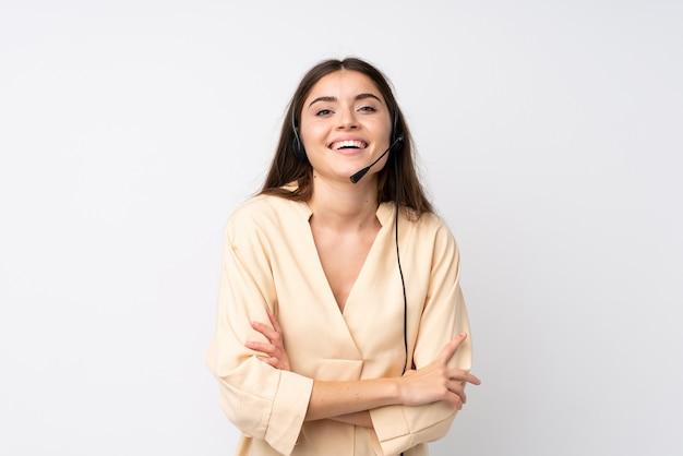 Młoda telemarketer kobieta śmia się nad odosobnionym biel ściany