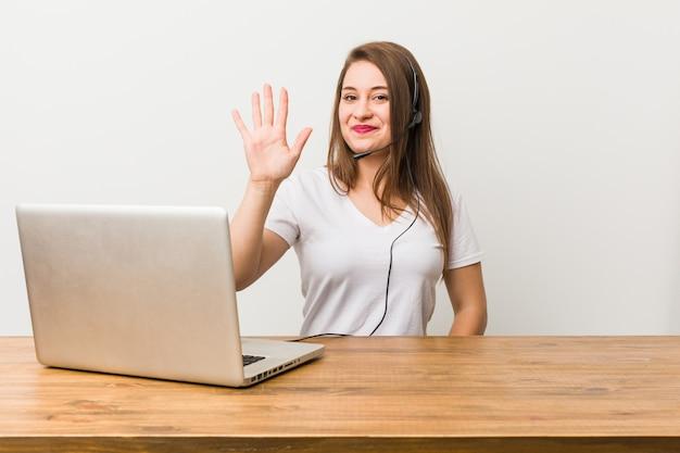 Młoda telemarketer kobieta uśmiecha się rozochoconego seans liczba pięć z palcami.