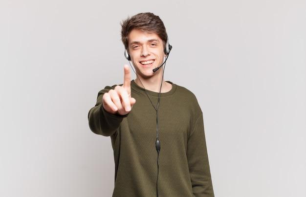 Młoda telemarketerka uśmiechnięta dumnie i pewnie wykonująca triumfalną pozę numer jeden, czując się jak lider