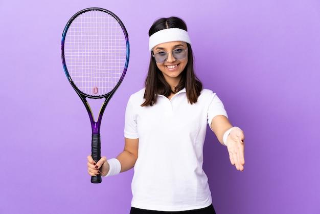 Młoda tenisistka kobieta na białym tle drżenie rąk za zamknięcie dużo