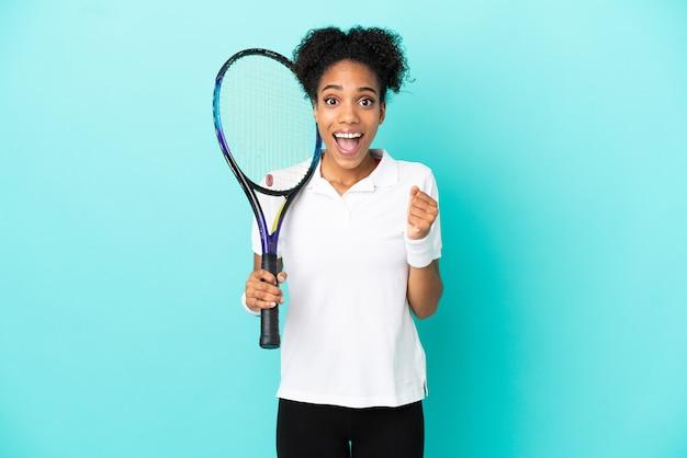 Młoda tenisistka na białym tle na niebieskim tle świętuje zwycięstwo w pozycji zwycięzcy