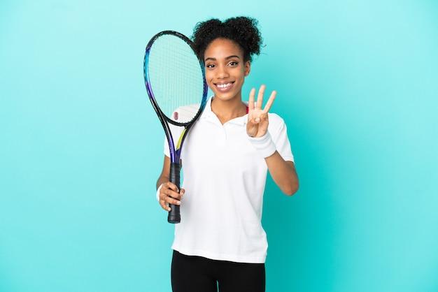 Młoda tenisistka na białym tle na niebieskim tle szczęśliwa i licząca trzy palcami