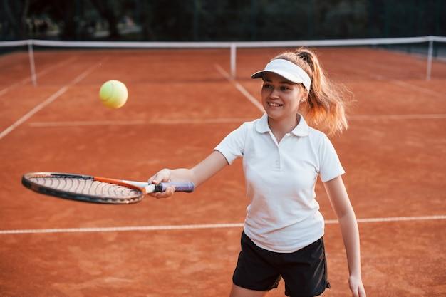 Młoda tenisistka w sportowej odzieży jest na boisku na zewnątrz.