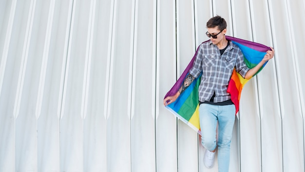 Młoda transpłciowa posiadająca flagę lgbt