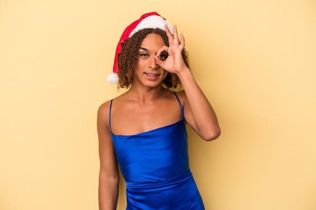 Młoda transseksualna kobieta z łaciny świętuje boże narodzenie na żółtym tle podekscytowany, zachowując ok gest na oku.