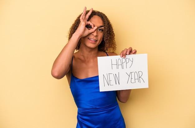 Młoda transseksualna łacińska kobieta świętuje nowy rok na białym tle na żółtym tle podekscytowany, zachowując ok gest na oku.