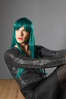 Młoda transseksualna osoba ubrana w zieloną perukę