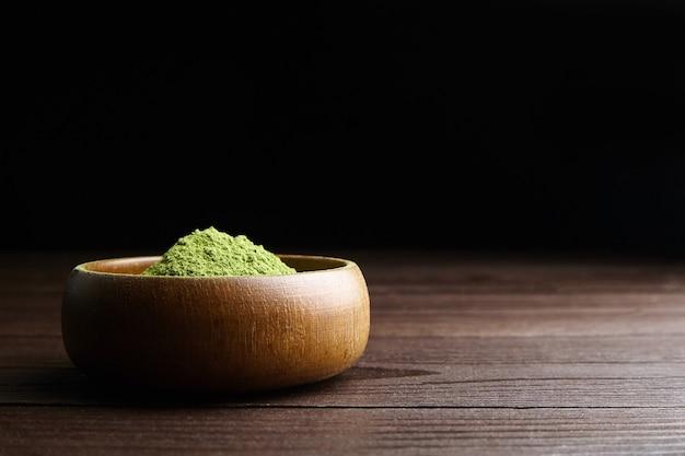 Młoda trawa pszeniczna lub jęczmienna w proszku w drewnianej misce na ciemnym tle. pożywienie detoksykacyjne