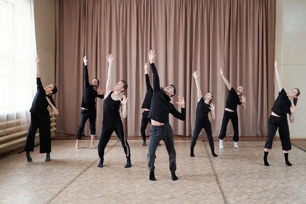 Młoda trenerka tańca pokazująca ćwiczenia kilkunastu chłopaków i dziewczyn w strojach sportowych podczas treningu w studiu baletu nowoczesnego