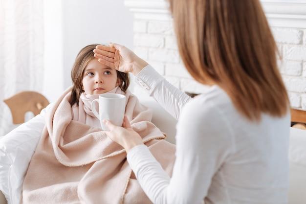 Młoda troskliwa matka trzyma filiżankę herbaty i opiekuje się córką, podczas gdy jej chora córka odpoczywa na kanapie