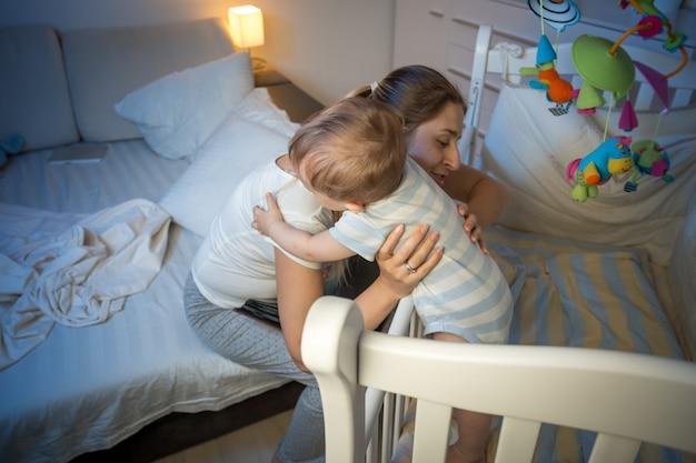 Młoda troskliwa matka wyjmująca dziecko z łóżeczka w nocy