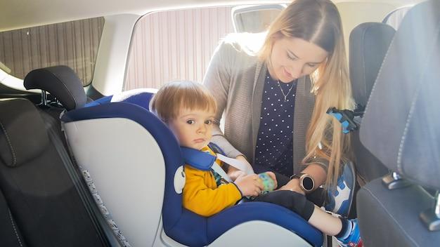 Młoda troskliwa matka zapina pasy w foteliku samochodowym swojego dziecka.