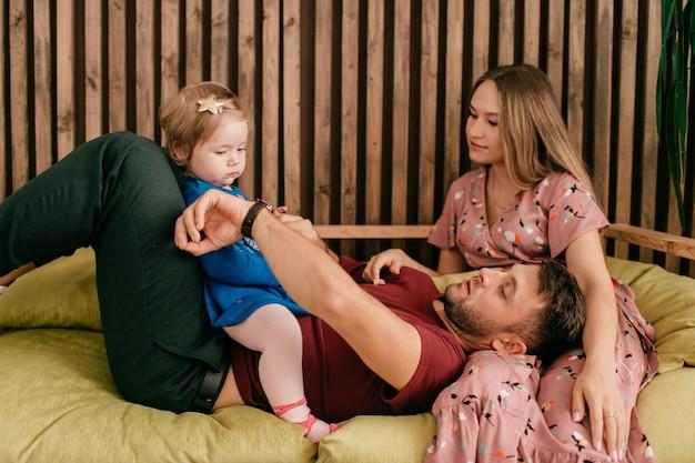 Młoda trzyosobowa kaukaska rodzina leży na kanapie i dobrze się bawi w weekend.