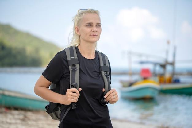 Młoda turystka blondynki z plecakiem na plaży z przyjemnością patrząca na piękny morski krajobraz, z bliska