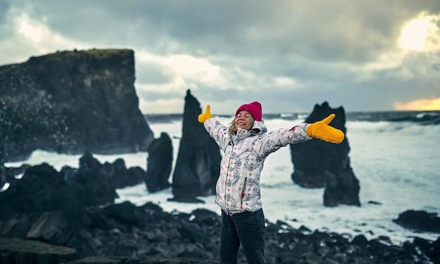 Młoda turystka fotograf kobieta w kapeluszu i rękawiczkach nad brzegiem morza w zimne i wietrzne dni, spaceruje wzdłuż czarnej wulkanicznej plaży bazaltowej ze skałami.