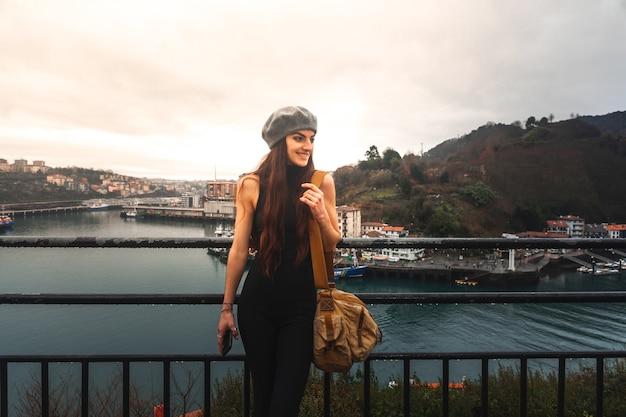 Młoda turystka kaukaska kobieta patrząca na zatokę z wysokiego punktu widzenia na pasaia; kraj basków.