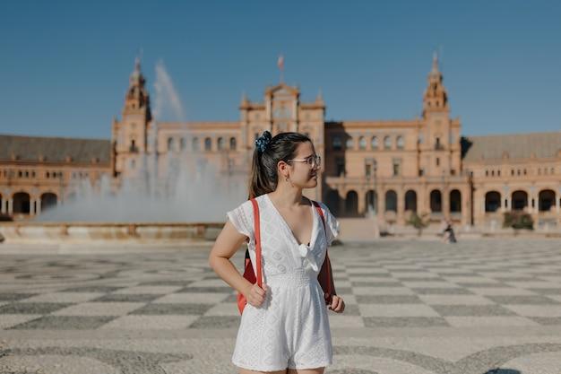 Młoda turystka w okularach, ubrana w białą sukienkę i czerwony plecak, odwraca wzrok i uśmiecha się