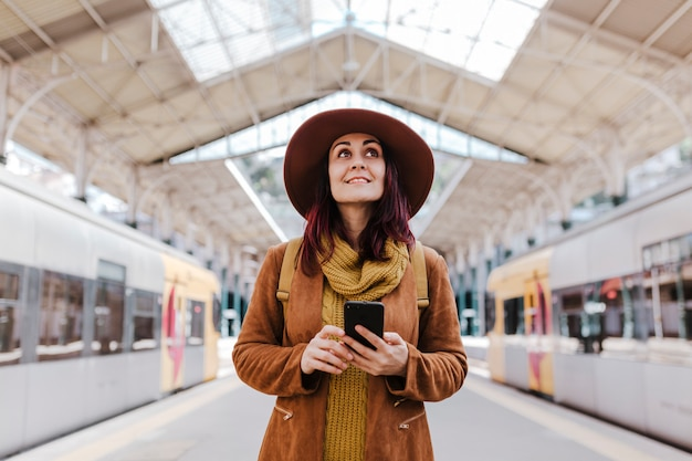 Młoda turystyczna kobieta czeka przy pociągiem i podróżuje przy dworcem. korzystanie z telefonu komórkowego i uśmiechanie się