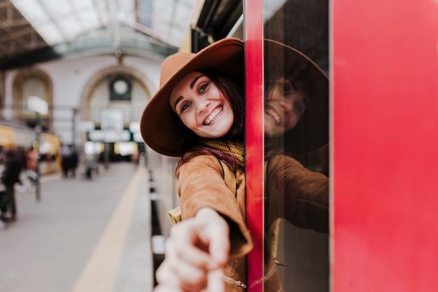 Młoda turystyczna kobieta czeka przy pociągiem i podróżuje przy dworcem. trzymając drugą rękę i patrząc w kamerę