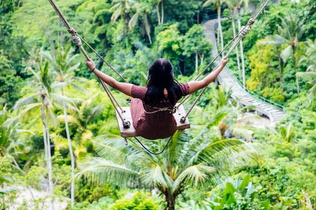 Młoda turystyczna kobieta huśta się nad tropikalnym lasem deszczowym przy bali wyspą