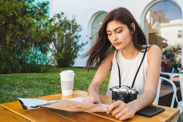 Młoda turystyczna kobieta patrzeje mapę przy sklep z kawą