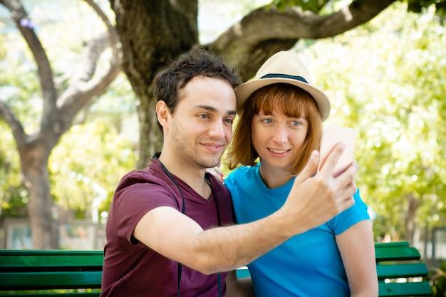 Młoda turystyczna para bierze selfie z telefonem komórkowym outdoors.