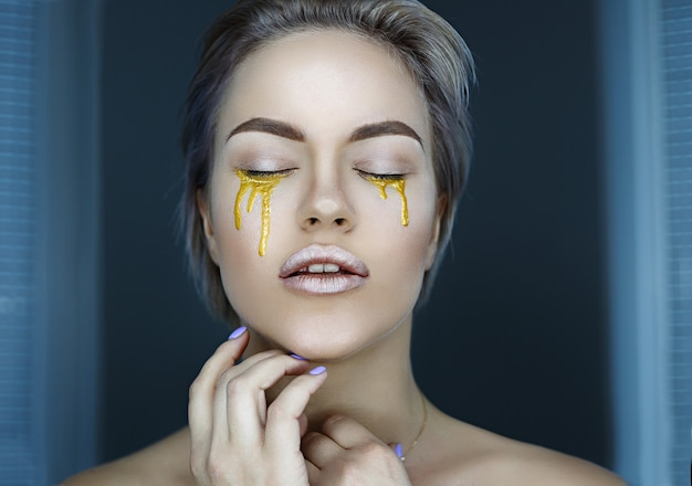 Młoda twarz kobiety z złoty makijaż artystyczny patrząc na aparat łzy zbliżenie widok z przodu