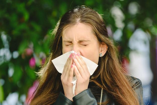 Młoda tysiącletnia chora kobieta kicha trzymając chusteczkę tkankową i dmuchając wycierając nos