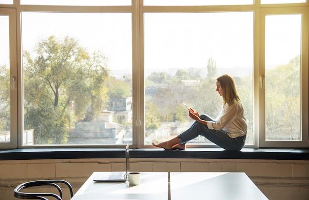 Młoda tysiącletnia dziewczyna patrzy w smartfonie, siedząc przy oknie w jasnym wnętrzu.