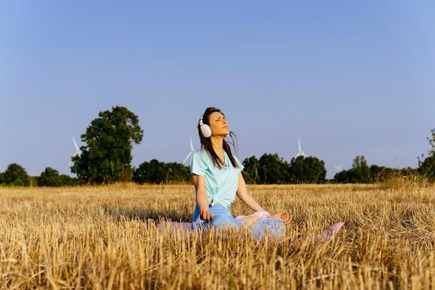 Młoda tysiącletnia kobieta w hełmach i odzieży sportowej robi jogę o zachodzie słońca w polu