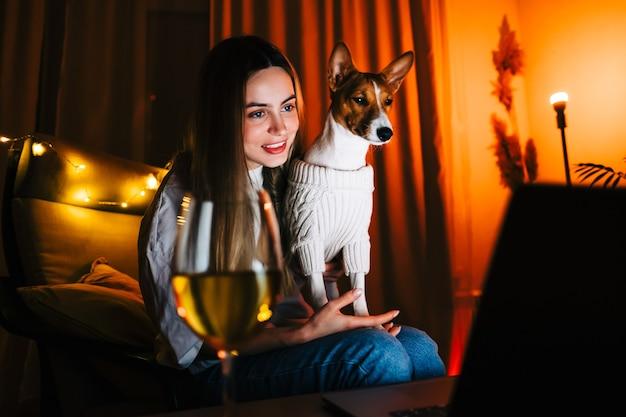 Młoda tysiącletnia kobieta z psem prowadzi rozmowę wideo na laptopie i pije wino, używa technologii do komunikowania się z przyjaciółmi lub rodziną.