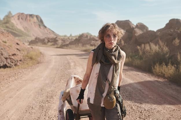 Młoda uchodźczyni w brudnych ubraniach z wózkiem na pustyni ucieka z niewoli