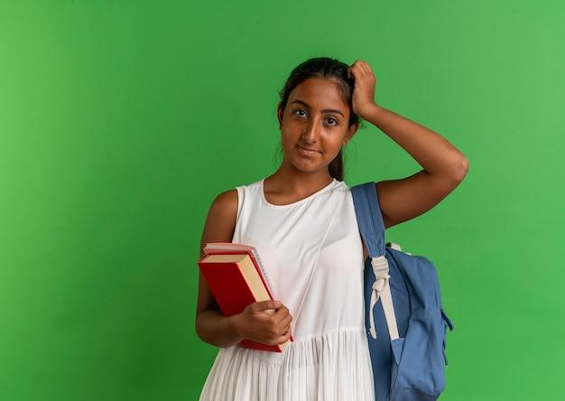 Młoda uczennica na sobie plecak trzymając książkę z notatnikiem i kładąc rękę na głowie