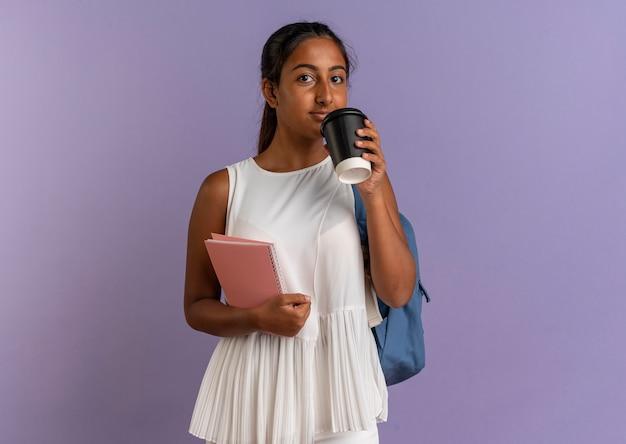 Młoda uczennica na sobie plecak trzymając notebook i filiżankę kawy