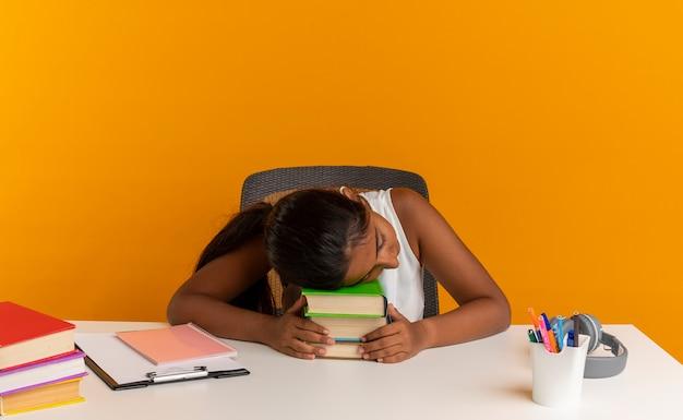 Młoda uczennica siedzi przy biurku z narzędzi szkolnych, kładąc głowę na książki samodzielnie na pomarańczowej ścianie