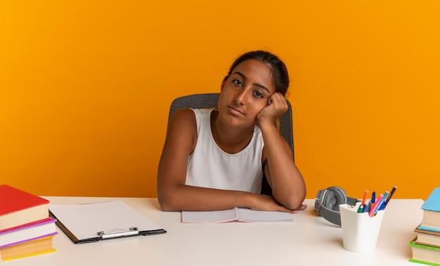 Młoda uczennica siedzi przy biurku z narzędzi szkolnych, kładąc głowę na rękę