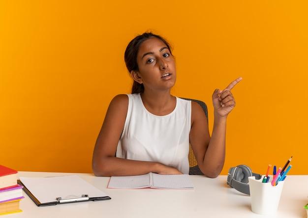 Młoda uczennica siedzi przy biurku z narzędzi szkolnych punktów na boku