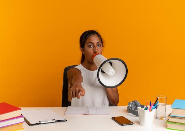 Młoda uczennica siedzi przy biurku z narzędziami szkolnymi mówi przez głośnik