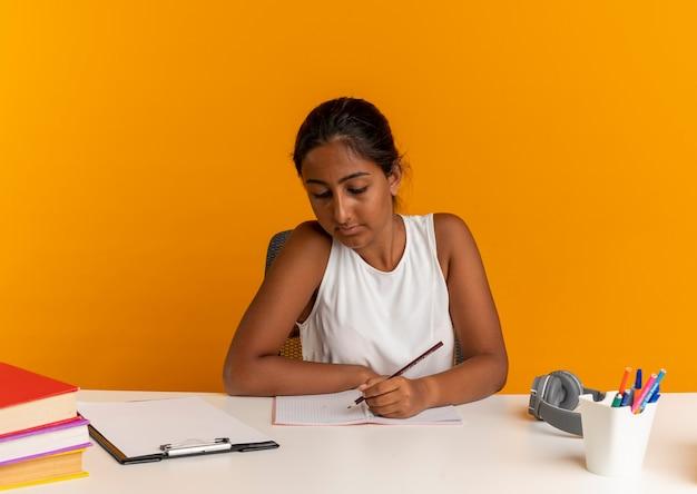 Młoda uczennica siedzi przy biurku z narzędziami szkolnymi napisać coś na notebooku na pomarańczowo