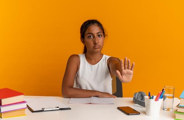 Młoda uczennica siedzi przy biurku z narzędziami szkolnymi pokazując gest zatrzymania