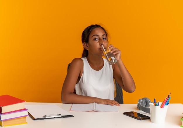 Młoda uczennica siedzi przy biurku z narzędziami szkolnymi wody pitnej