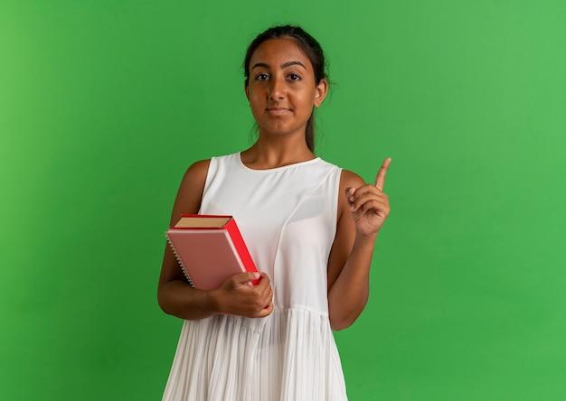 Młoda uczennica trzyma książkę z notatnikiem i wskazuje na górę