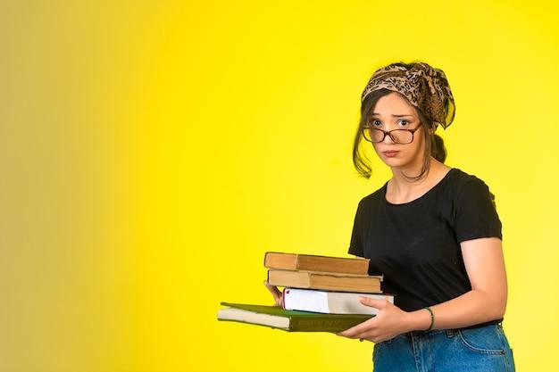Młoda uczennica w okularach trzyma książki i patrzy niewinnie.