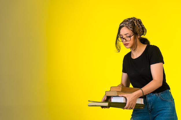 Młoda uczennica w okularach, trzymając jej książki na żółtym tle.