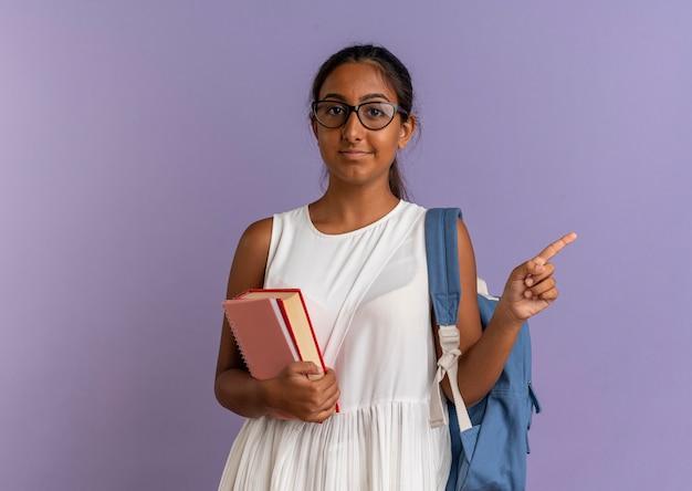 Młoda uczennica w plecaku i okularach, trzymając książki i wskazuje na bok