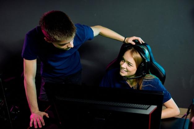 Młoda uczestniczka e-sportu, siedząca w fotelu gracza i rozmawiająca z nią o postępach w grach wideo