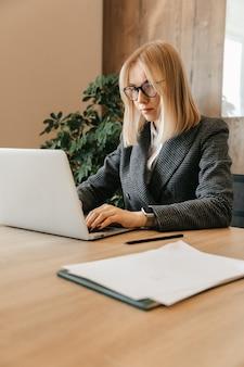 Młoda udana biznesowa kobieta siedzi w miejscu pracy w biurze. pracownik centrum biznesowego. wolny strzelec pracujący w internecie na komputerze.