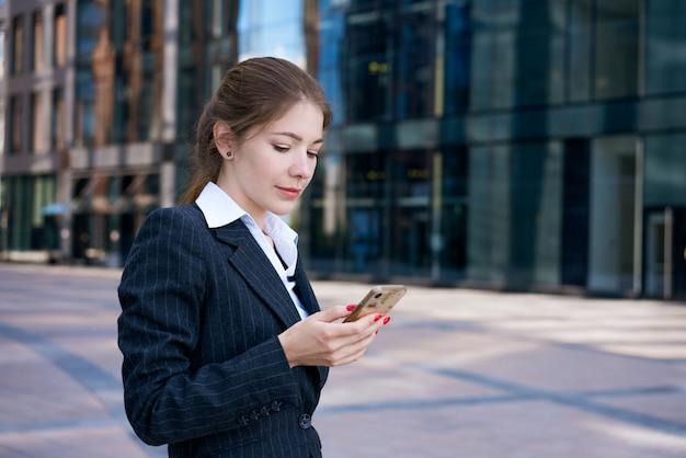 Młoda udana biznesowa kobieta z telefonem w dłoniach