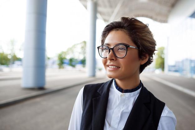 Młoda udana bizneswoman uśmiechnięta, stojąca w pobliżu centrum biznesowego