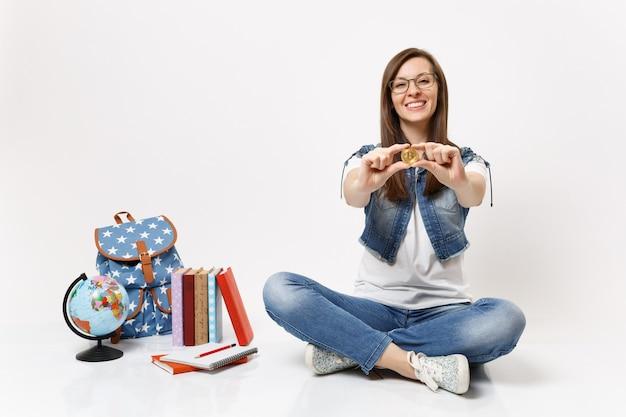 Młoda udana wesoła studentka dorywcza w okularach trzymająca bitcoina siedząca w pobliżu kuli ziemskiej, plecaka, podręczników szkolnych na białym tle
